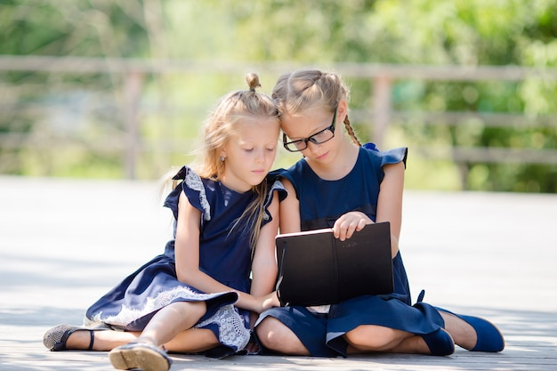 Adorable little school girls outdoors in warm september day. back to school.