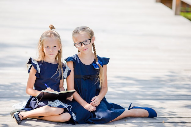 Adorable little school girls with notes and pencils outdoor. back to school.
