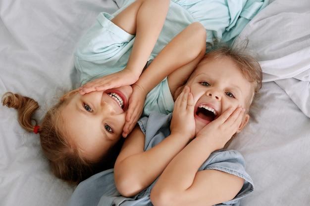 Очаровательные сестрички, лежа в постели, вид сверху