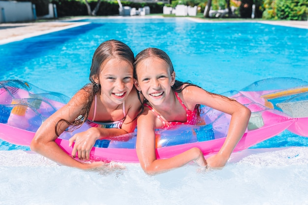 Adorable little sisters play in outdoor swimming pool
