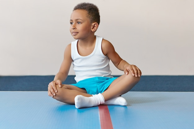 Adorable little sportsman of african appearance sitting on mat with legs crossed relaxing after intensive training.