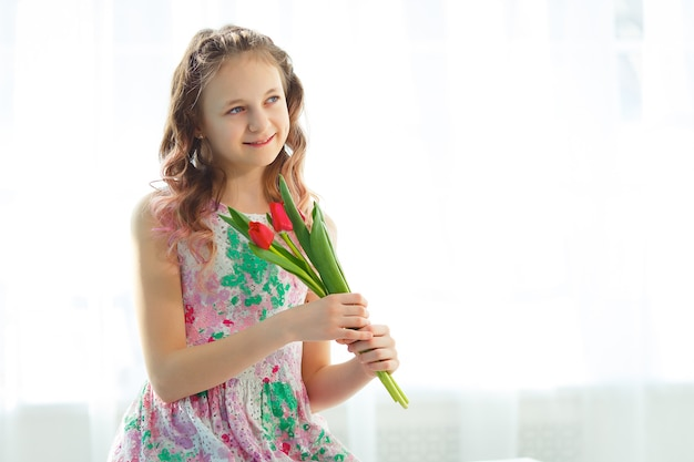 窓に座ってチューリップを持っている愛らしい小さなティーンエイジャーの女の子。少女は青く純粋な空を見て、春と太陽を喜ぶ。