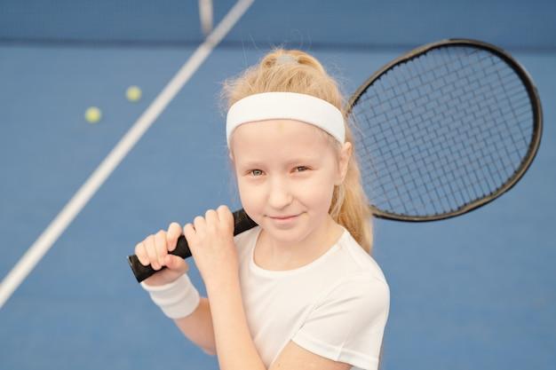スタジアム環境でカメラの前に立っている間、右肩にラケットを保持している白いアクティブウェアの愛らしい小さなテニスプレーヤー