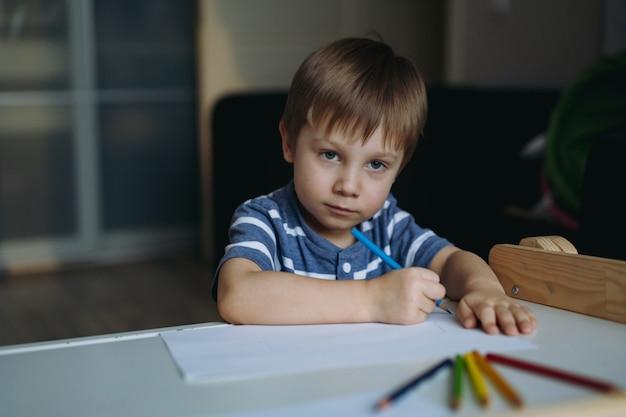 Очаровательный маленький мальчик, страстно рисующий цветными карандашами изображение с выборочным фокусом