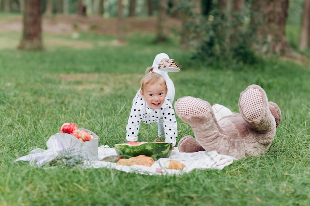 Adorable little toddler girl with a big teddy bear having fun in the summer park on sunny day. concept of summer holiday picnic. selective focus.