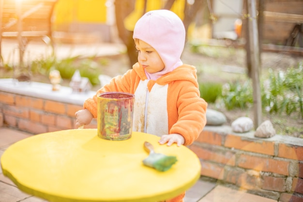 Adorable little toddler paints illuminated yellow round table with brush