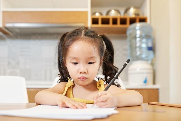 Очаровательная маленькая вьетнамская девочка сидит за кухонным столом и рисует карандашом