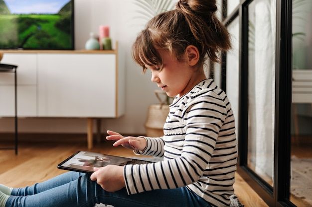 Adorable little woman in good mood watches cartoons in tablet and poses in living room.
