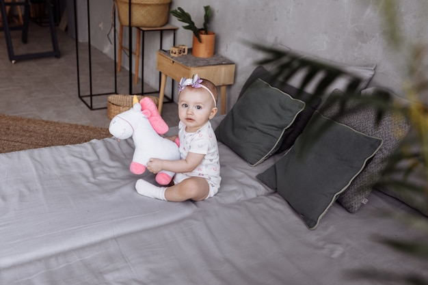 Adorable little woman is playing with toy unicorn on bed at home. concept of childhood day. happy baby's, family day