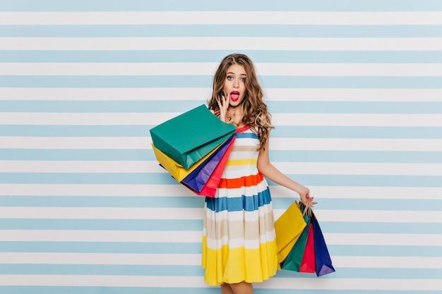 Очаровательны длинноволосый женский шопоголик позирует с удивленным выражением лица. пораженная молодая женщина с красочными сумками из магазина изолирована на полосатой стене.