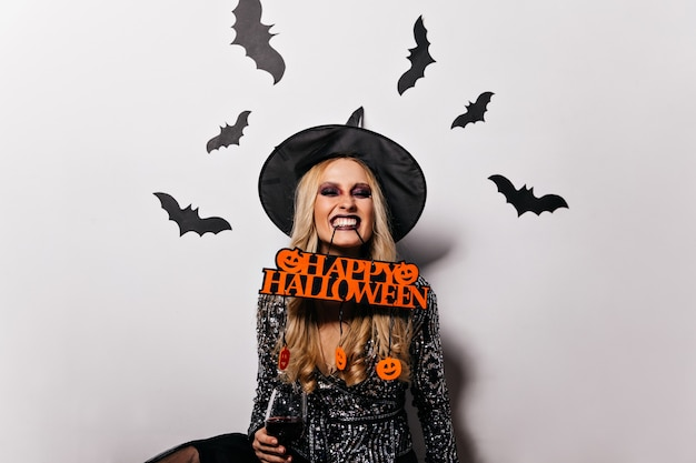 Adorabile donna dai capelli lunghi in posa di halloween con i pipistrelli sul muro. meravigliosa ragazza strega divertendosi al carnevale.