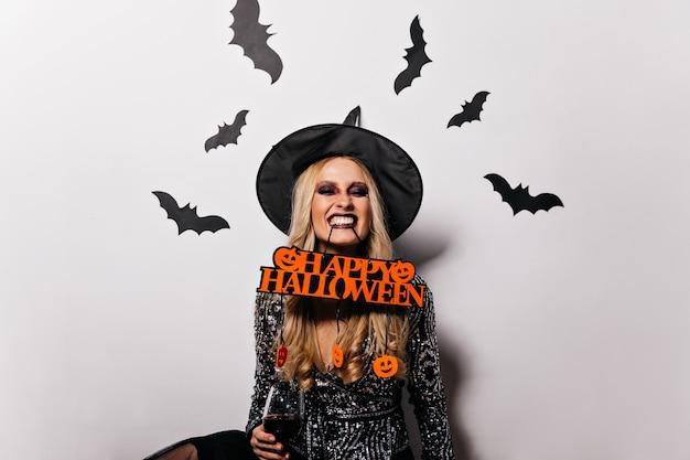 벽에 박쥐와 할로윈에 포즈를 취하는 사랑스러운 긴 머리 여자. 카니발에서 재미 멋진 마녀 소녀입니다.