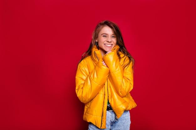 Очаровательная милая счастливая женщина с длинными волосами в ярко-желтой зимней куртке позирует на красной стене