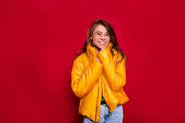 Adorable lovely happy woman with long hair wearing bright yellow winter jacket posing on red wall