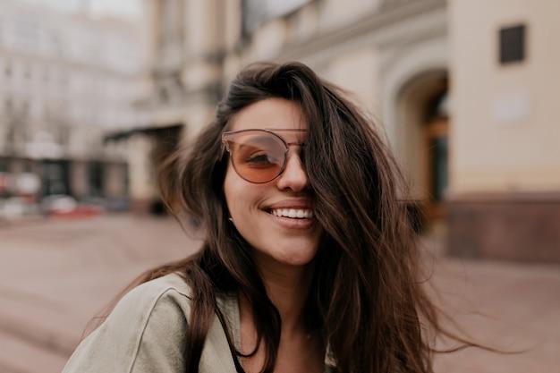通りを歩きながら屋外のカメラでポーズをとってファッションメガネをかけて黒髪の愛らしい素敵な女性