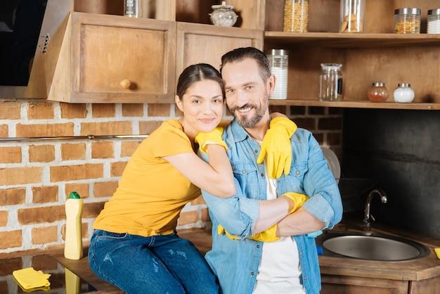 手袋をはめて抱きしめながら直接見ている愛らしい愛情のある誠実なカップル
