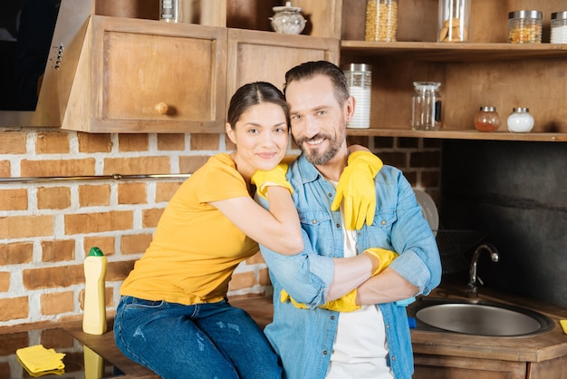 Adorable loving sincere couple looking directly while hugging and wearing gloves