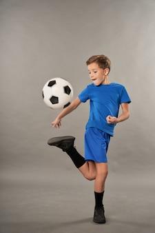 灰色の背景に対してサッカーのトリックをしているショートパンツの愛らしい男性の子供