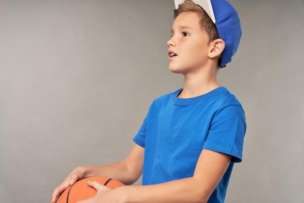 バスケットボールのボールを保持し、目をそらしながら青いシャツとキャップを身に着けている愛らしい男子
