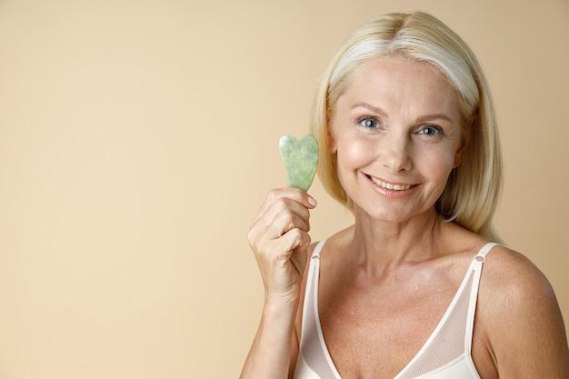 Очаровательная зрелая блондинка в белом лифчике улыбается в камеру и держит инструмент для массажа нефрита гуа ша