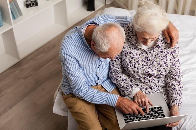 Adorable mature couple using a laptop