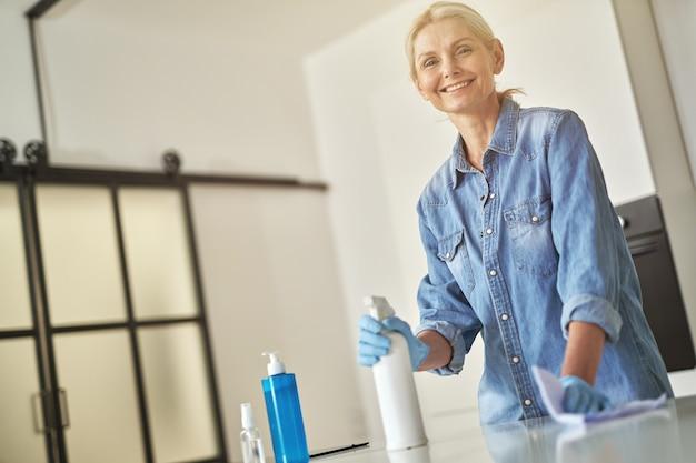 洗剤スプレーと布を使用してカメラに微笑んでいる間ゴム手袋で愛らしい成熟した女性