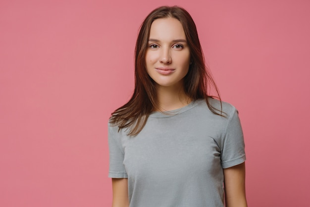 Adorable millennial girl with straight dark hair, wears casual t shirt, looks seriously at camera, has healthy skin, poses over pink background. pleasant looking woman has talk with someone.