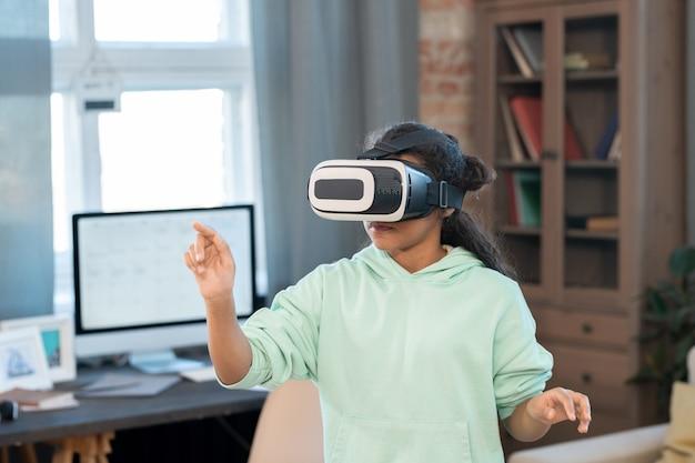 Очаровательная девушка смешанной расы в гарнитуре vr трогает виртуальный дисплей во время просмотра онлайн-видео перед камерой в домашней обстановке