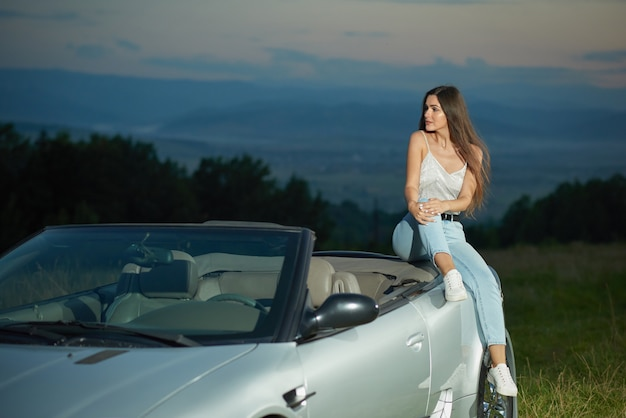 Adorable model sitting on silver cabriolet and looking away.