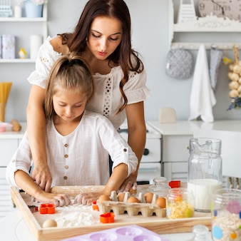 Adorable mother and daughter preparing cookies