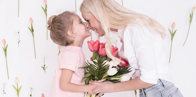 Adorable mother and daughter  with tulips