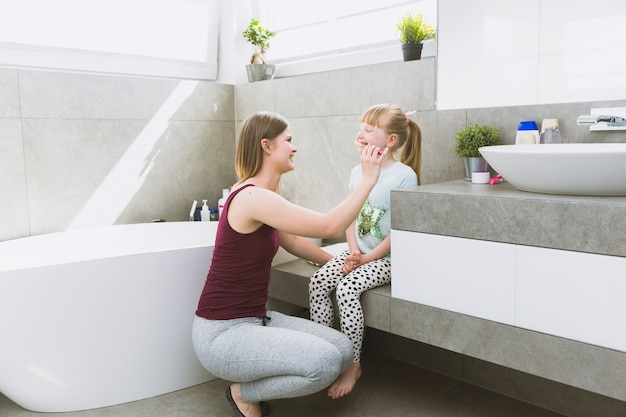 Adorable mother helping daughter with brushing teeth