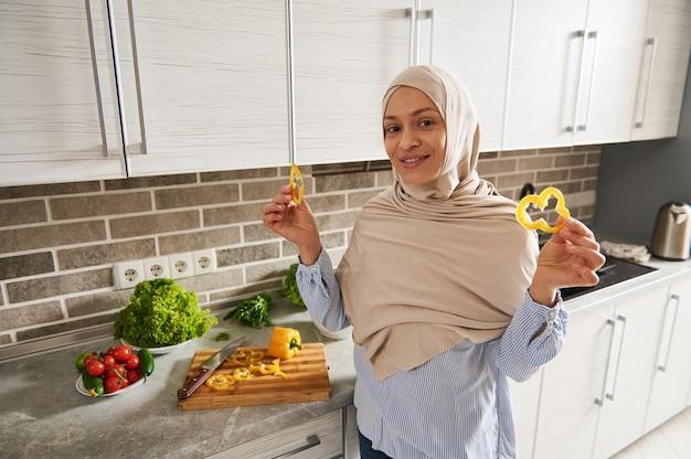 귀여운 hijab의 사랑스러운 무슬림 여성은 채식주의 샐러드를 요리하는 동안 그녀의 손에 노란 고추 조각을 들고 카메라에 미소를 짓습니다.