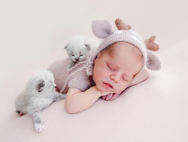 배 위에서 자고 있는 사랑스러운 갓난 아기와 그 옆에 앉아 있는 솜털 같은 새끼 고양이 두 마리. 스튜디오 사진 촬영 중 고양이와 낮잠을 자는 모자와 니트 의상을 입은 귀여운 유아