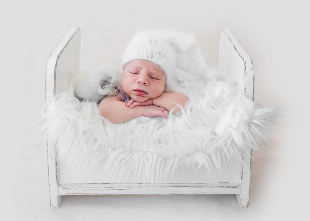 작은 솜털 고양이와 모피와 흰색 나무 침대에서 그의 뱃속에 잠자는 사랑스러운 갓난 아기. 스튜디오 사진 촬영 중 고양이 키티와 함께 낮잠을 자는 니트 모자를 쓴 귀여운 유아 아이