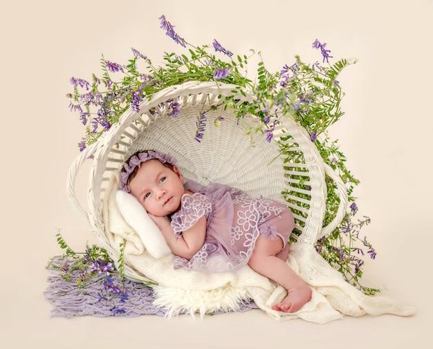 Очаровательная новорожденная девочка в красивом платье и венке, лежащая в корзине с растительным украшением, держась за руки под ее щеками в студии. милый младенец с цветами