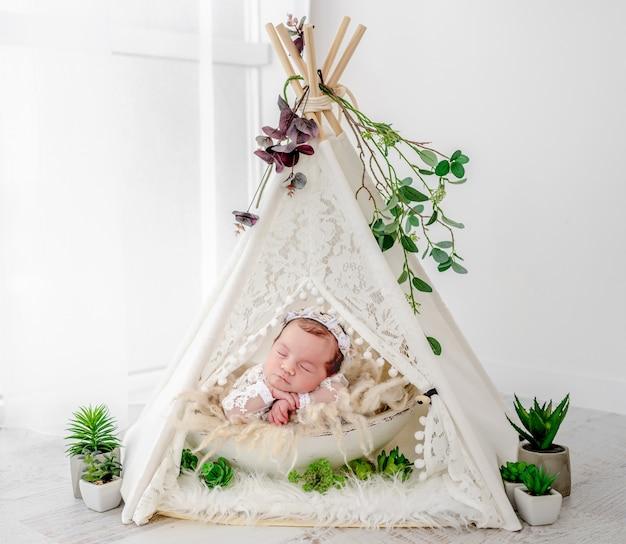 아름다운 드레스와 화환을 입은 사랑스러운 갓난 아기 소녀는 스튜디오에서 그녀의 뺨 아래에 손을 잡고 있는 식물 장식으로 오두막 wigwam에 누워 있습니다. 모피에 낮잠 귀여운 유아 아이
