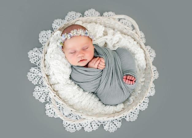 사랑스러운 갓난 아기 소녀는 화환을 바구니에 등을 대고 누워 자고 있습니다. 장식과 함께 스튜디오 사진 촬영 중 낮잠을 자는 천으로 싸인 달콤한
