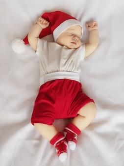 Очаровательны новорожденного в костюме рождества санта-клауса, спящего на белом листе