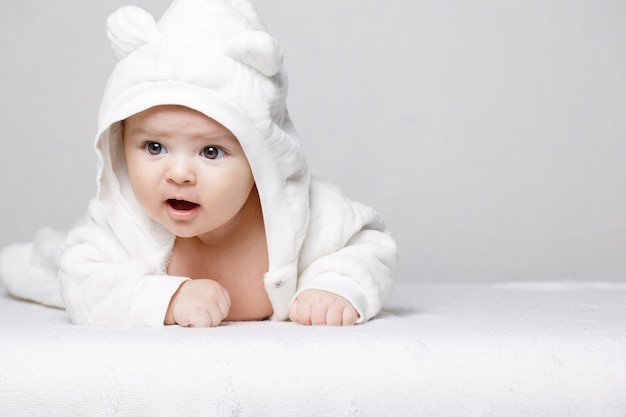 Adorable newborn baby in a soft suit on white background
