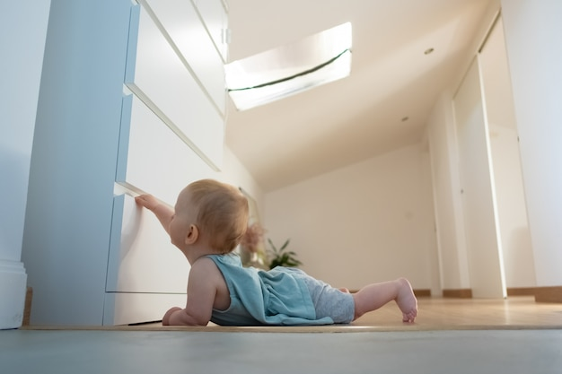 Adorable newborn opening closed wardrobe and lying on belly on wooden floor with barefoot. side view of cute red-haired infant exploring room at home. childhood and infancy concept