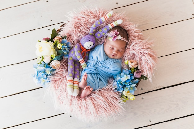Adorable newborn with toy sleeping in basket