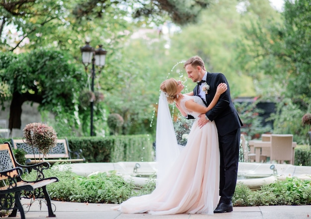 Adorable newlyweds hug each other tender posing before a fountain in the garden