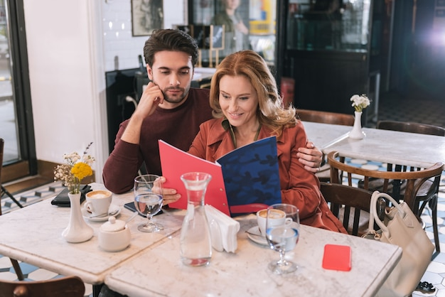 Adorable nice couple reading menu and sitting at table