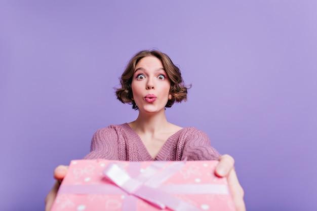 Очаровательная бледная женщина позирует с выражением лица целуя и держит подарок на день рождения. заинтересованная молодая леди, изолированные на фиолетовой стене с подарком на новый год.