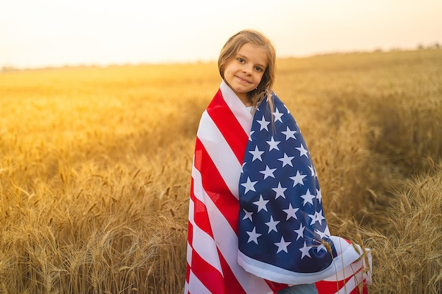 Adorable patriotic girl wearing an american flag in a beautiful wheat field.