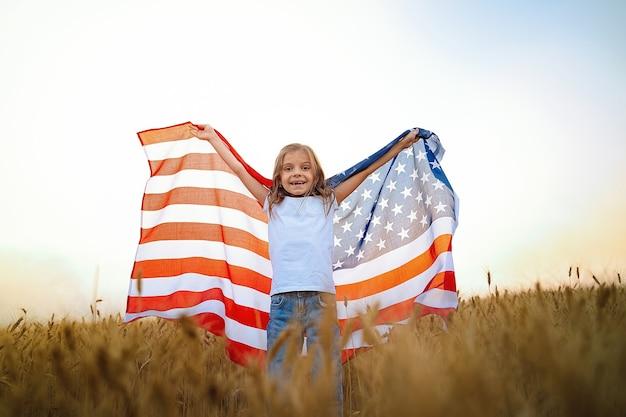 아름다운 밀밭에 미국 국기를 입고 사랑스러운 애국 소녀.