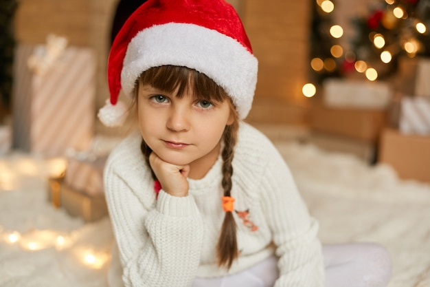 Adorable pensive female child waiting for christmas, little girl in santa hat wearing white jumper, looks at camera, keeps hand under chin, posing in festive room.