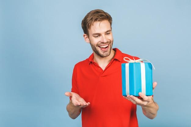 Очаровательное фото привлекательного мужчины с красивой улыбкой, держащего подарочную коробку на день рождения