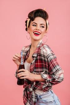 幸せを表現する愛らしいピンナップガール。ピンクの背景に飲み物を飲む素晴らしいブルネットの女性。